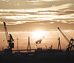 Germany, Hamburg, Silhouettes of harbour cranes at sunset, Koehlbrand bridge in the background - KRPF001409