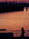 Germany, Hamburg, Port of Hamburg, young female photographer standing on Elbe riverside at sunset - KRPF001412