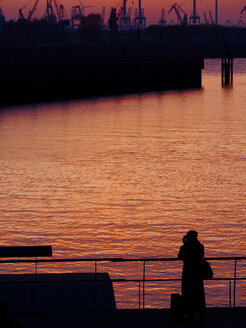 Germany, Hamburg, Port of Hamburg, young female photographer standing on Elbe riverside at sunset - KRPF001412