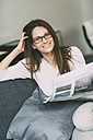 Portrait of smiling woman sitting on couch with newspaper - RZDF000012