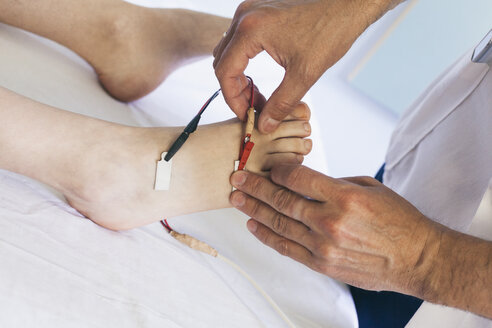 Chiropractor performing a foot electrotherapy - BZF000100