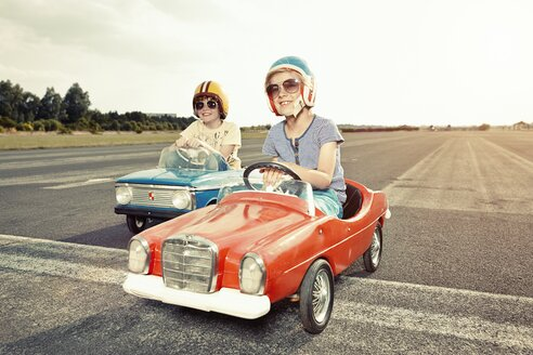 Two boys in pedal cars crossing finishing line on race track - EDF000160