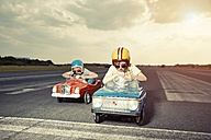 Two boys in pedal cars crossing finishing line on race track - EDF000163