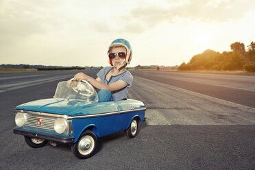 Boy with sunglasses in pedal car on race track - EDF000169