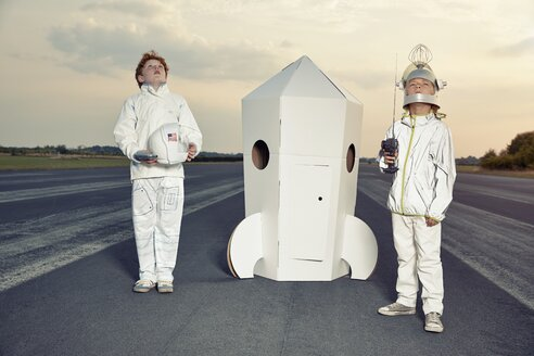 Two boys dressed up as spacemen standing at cardboard rocket - EDF000148