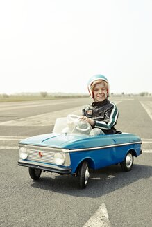 Smiling boy in pedal car on race track - EDF000177