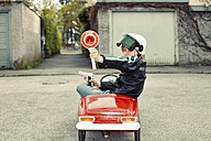 Boy in pedal car dressed up as policeman - EDF000180