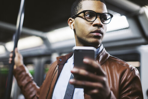 Businessman with smartphone on the subway train - EBSF000482