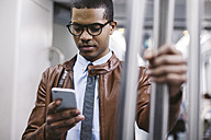 Businessman with smartphone on the subway train - EBSF000488