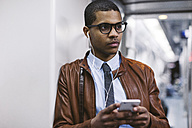 Portrait of businessman with smartphone and earphones hearing music on the subway train - EBSF000491