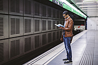 Spain, Barcelona, businessman standing at underground station platform reading book - EBSF000499
