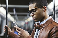 Portrait of businessman with smartphone and earphones hearing music on the subway train - EBSF000506
