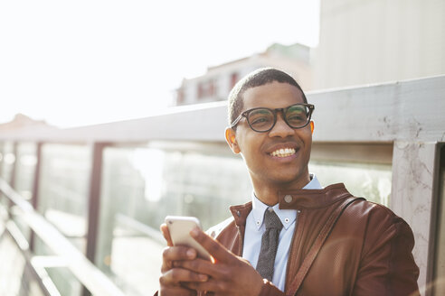 Portrait of smiling businessman with smartphone wearing leather jacket and glasses - EBSF000519