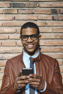 Portrait of smiling businessman with smartphone wearing leather jacket and glasses - EBSF000532