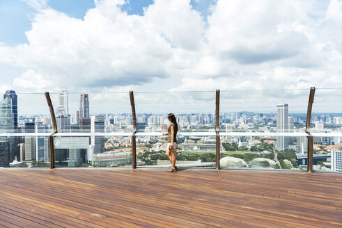 Singapore, woman standing on observation deck of Sands SkyPark looking at view - GEM000166