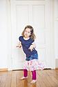 Girl dancing at wooden door - LVF003159