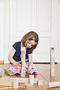 Little girl crouching on floor playing with wooden building bricks - LVF003150