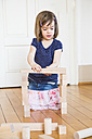 Little girl crouching on floor playing with wooden building bricks - LVF003152