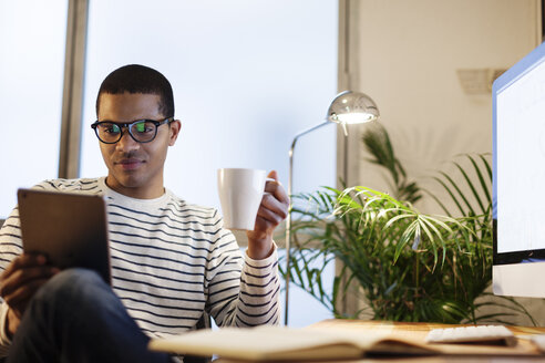 Young creative man with mini tablet having coffee break in his home office - EBSF000549