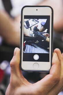 Man's hand holding smartphone with photography of tattoo artist at work - SELF000015