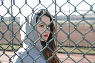 Portrait of woman with hooded jacket behind mesh wire fence - BFRF001065