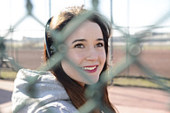 Portrait of smiling woman with headphones behind mesh wire fence - BFRF001067