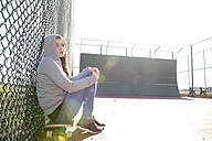 Sad woman sitting on her skateboard on a sports field - BFRF001068