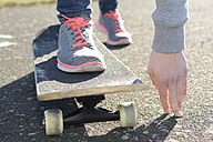 Hand and sneakers of woman on skateboard - BFRF001072