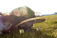 Portrait of young woman lying on skateboard on a meadow - BFRF001074