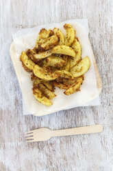 Baked potato wedges with herbs and parmesan on greaseproof paper and wooden plate - EVGF001477