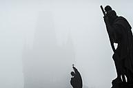 Czech Republic, Prague, statue on Charles Bridge in morning fog - HAMF000037