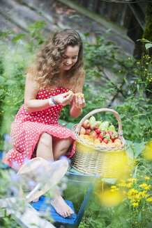 Smiling young woman with with wire basket of different fruits in a garden - HHF005287