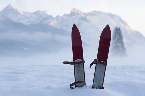 Germany, Bavaria, pair of children's ski in snow in front of Karwendel mountains - ASF005551