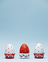 Coloured Easter eggs in paper cups in front of light blue background - BZF000128