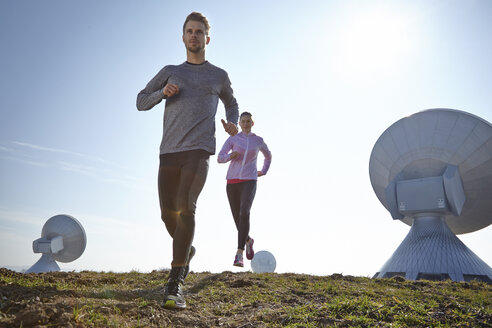 Germany, Raisting, young couple jogging at ground station - KDF000706