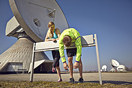 Germany, Raisting, young jogger couple having a rest at ground station - KDF000714
