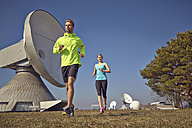 Germany, Raisting, young couple jogging at ground station - KDF000716
