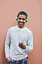 Portrait of smiling young man hearing music with green headphones - EBSF000566