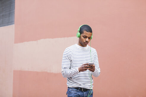 Young man hearing music with green headphones - EBSF000569
