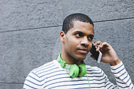 Portrait of young man with green headphones telephoning with smartphone - EBSF000570