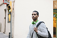 Young man with green headphones and backpack on street - EBSF000572