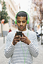 Spain, Barcelona, young man hearing music with green headphones on street - EBSF000577