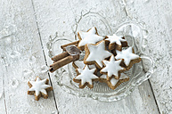 Glass bowl of cinnamon stars and cinnamon sticks - ASF005569