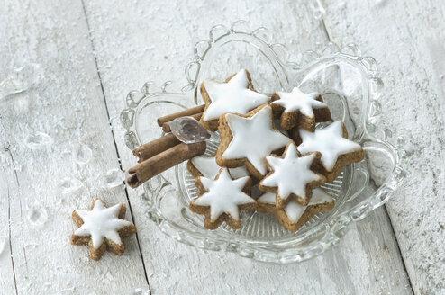 Glass bowl of cinnamon stars and cinnamon sticks - ASF005569