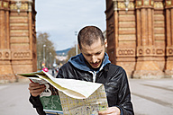 Spain, Barcelona, man looking at city map in front of trymphal arch - GEMF000180