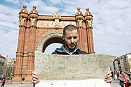Spain, Barcelona, man looking at city map in front of trymphal arch - GEMF000182