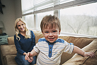 Portrait of smiling little boy with his mother in the background - SELF000037