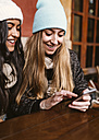 Two young women sending message with smartphone - MGOF000196