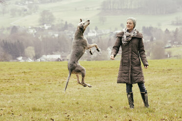 Woman exercising with dog on meadow - ONF000806