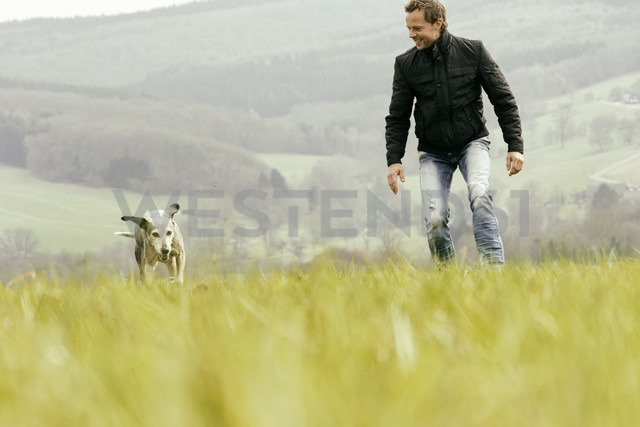 Man exercising with dog on meadow - ONF000809